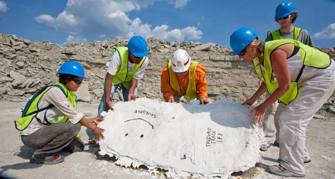 From left, Boise State University researcher Celina Suarez and University of Arkansas researchers Terryl Daniels, Stephen K. Boss and Joann Kvamme lift a dry plaster cast of a side-by-side sauropod and theropod print.