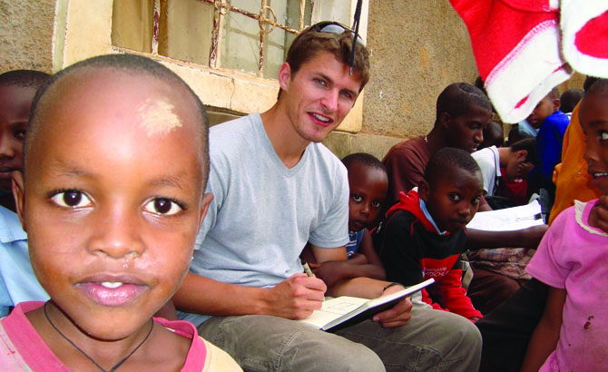 Andrew Arkell sketches in a Kigali neighborhood while inquisitive children look on.