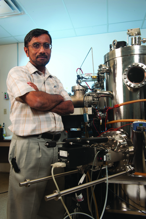 Hameed Naseem, professor of electrical engineering, with the semiconductor cluster tool that grad student Seth Shumate used when he discovered self-aligned hydrogenated selective emitter for N-type solar cells. [Photo by Logan J. Webster]