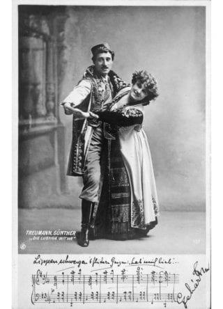 """Rollenbild in Lehars Operette """"Die Lustige Witwe"""", zusammen mit Mizzi Günther. Ganze Figur stehend, fast en face.  Künstlerpostkarte."""