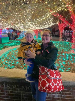 Katherine and child in front of Christmas lights