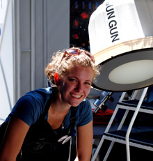Young woman beside a sun viewer that projects sun's light onto a screen.