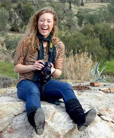 Young adult woman sitting on a rock with camera in hand