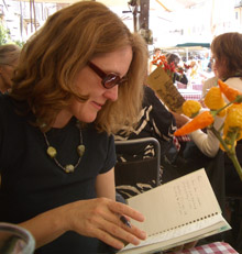 Woman in black t-shirt, sunglasses sits at outdoor cafe in Rome, writing.