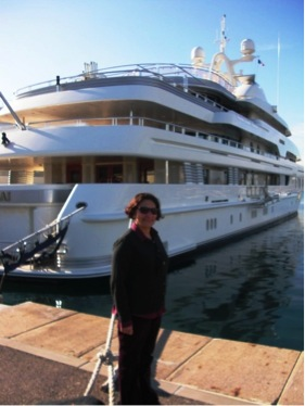 Woman stands in front of a very grand yacht.