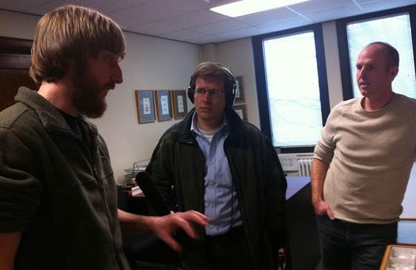 Bearded student gestures towards tray of mounted ants while interviewer and faculty mentor look on.