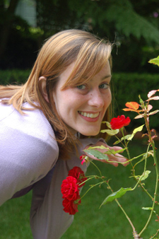Student, smiling, leans forward to smell red roses growing on rosebush.