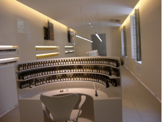 A sleek lab within the factory, with vials of scent on shelves.