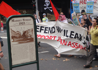"""Group of demonstrators carry banner that says """"Defend WikileaksSupport Julian Assange."""""""