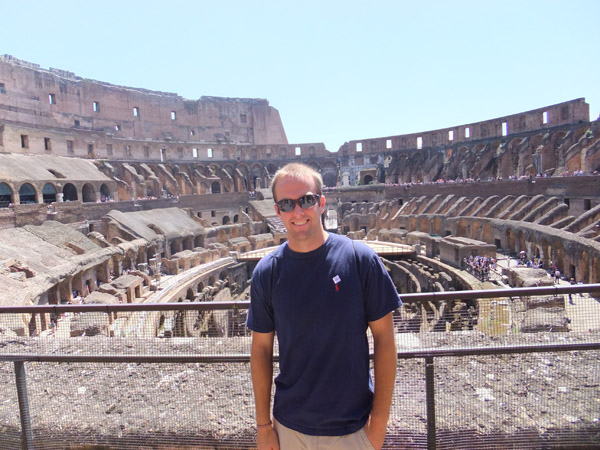 A young man in shades and navy t-shirt stands in front of the Roman Coliseum.