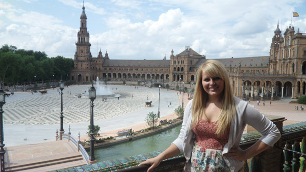 Young woman poses on balcony in front of a plaza with fountain in the center.