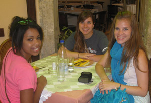 Three young women are seated at a table in a cafe.