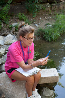 Woman in pink t-shirt, shorts is seated by a stream, reading a blue meter.