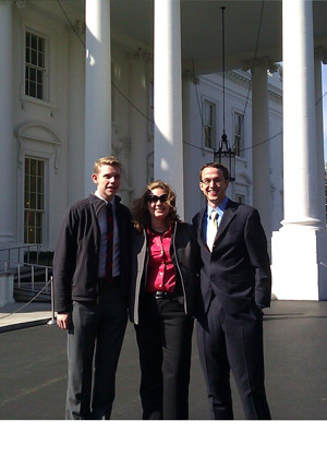 Two young men flank a young woman in bright red shirt; they're standing in front of the White House.