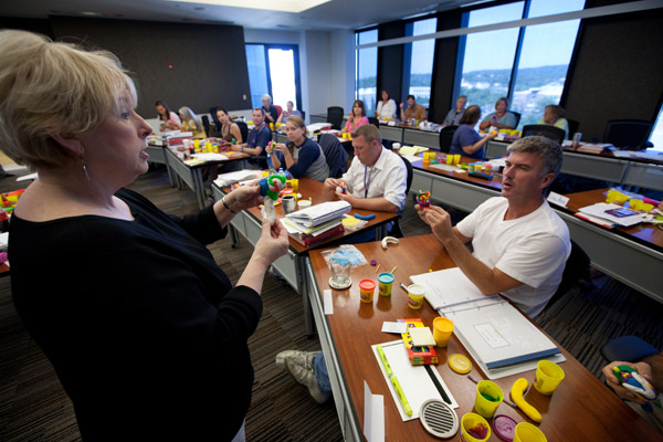 Woman demonstrates a brain modeled from Play-Doh to a roomful of teachers following her lead.