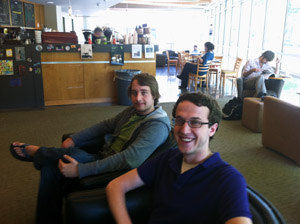 Two young men are seated in a coffee shop.