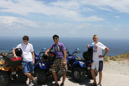 Three young men stand next to their ATVs as they overlook the Mediterranean