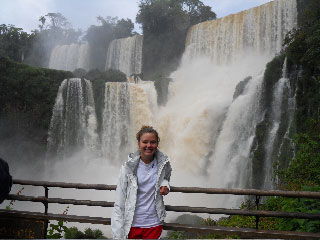 Young woman in front of a series of spectacular waterfalls.
