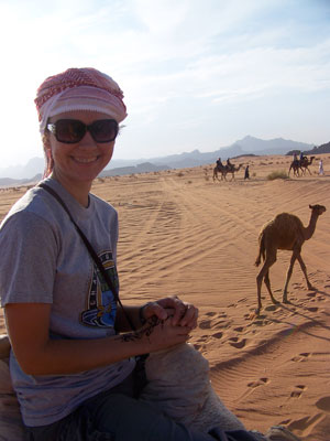 A young woman in cap and sunglasses is seated atop a camel, in the desert.