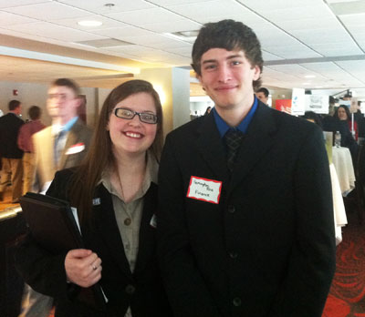 Female and male student, both in business dress and nametags, pose for their picture at career fair.