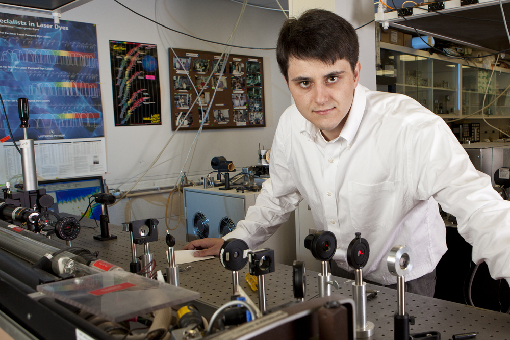 Young man in white shirt is photographed in a lab.