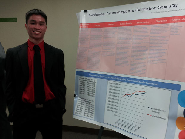Young man in suit stands next to research poster.