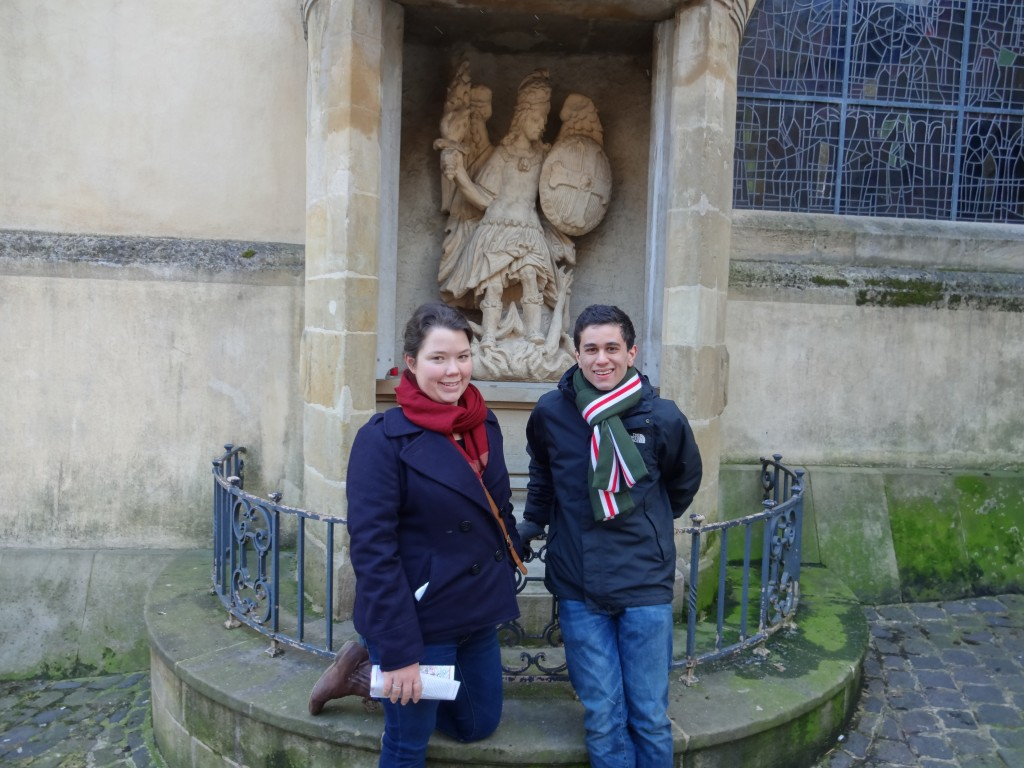 Matthias Bellaiche and Jessie Hargis pose with a statue of St. Michael the dragon slayer, one of the oldest shrines in the city dating back to the 900s.