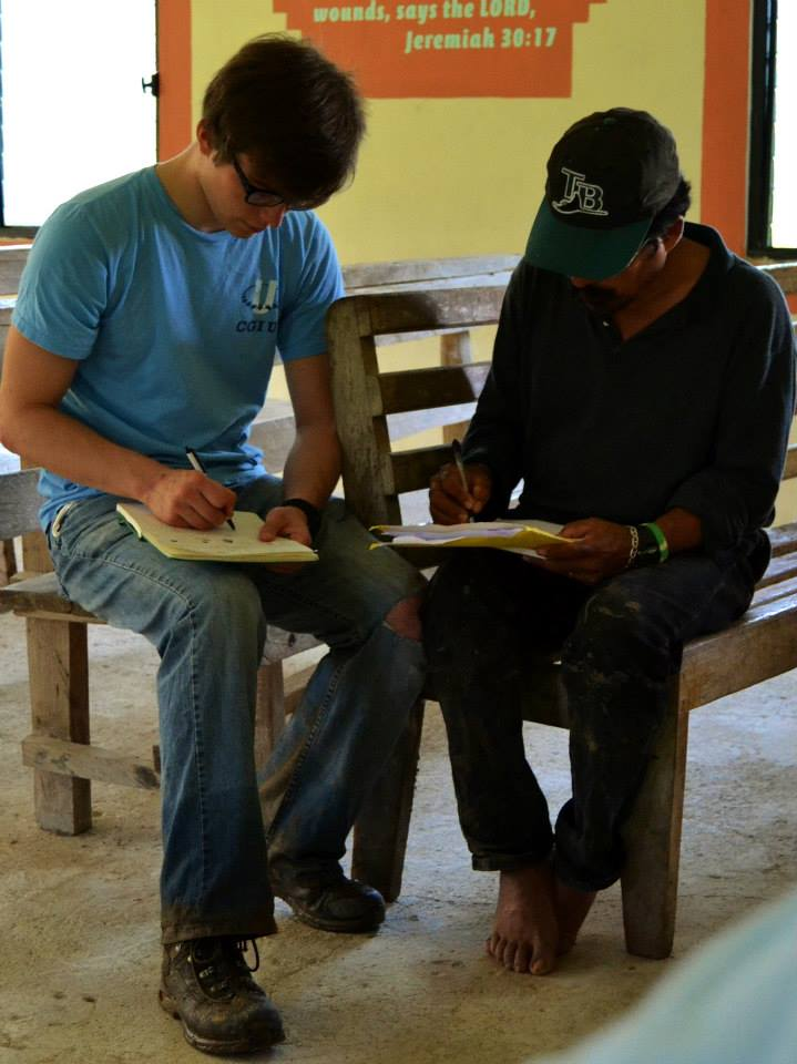 UA student and a villager from More Tomorrow, Belize, are working on notes together.
