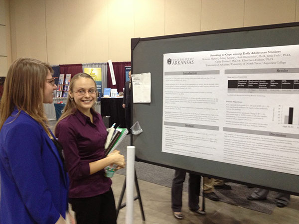 Two women stand in front of a research poster.