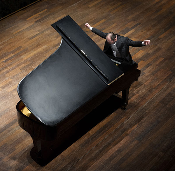 Pianist is performing at a grand piano, arms outstretched above the keyboard.