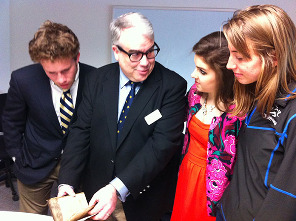 A professor and three students examine a small, leather-bound manuscript.