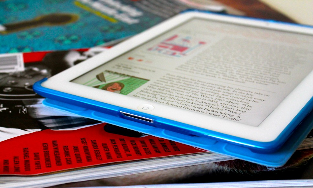 photo shows pile of magazines with iPad on top, showing page from digital magazine