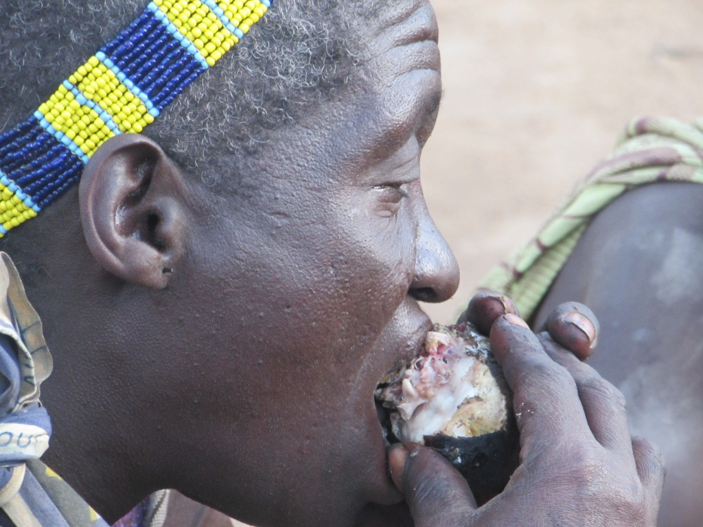 Hadza woman eats meat over a fire