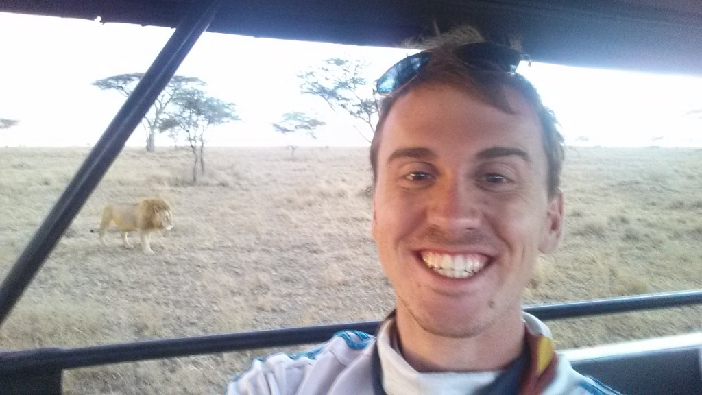man takes a self-portrait in a safari vehicle with a lion in the background