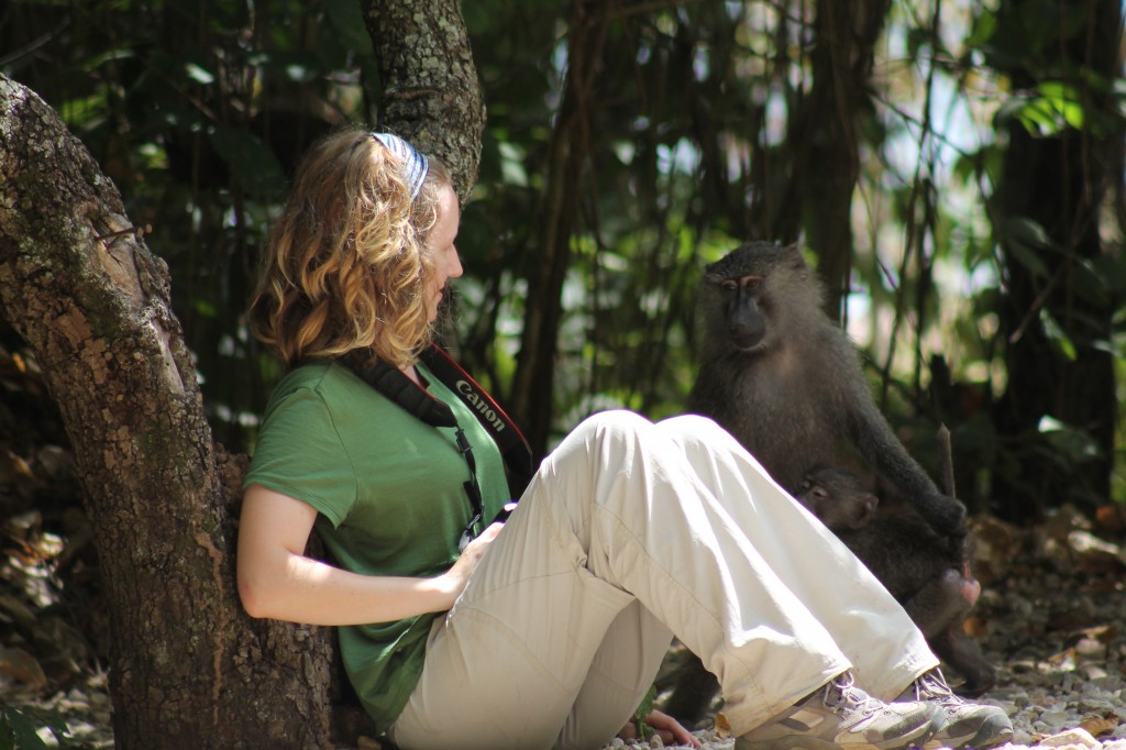 Girl sits still as a baboon approaches her curiously.