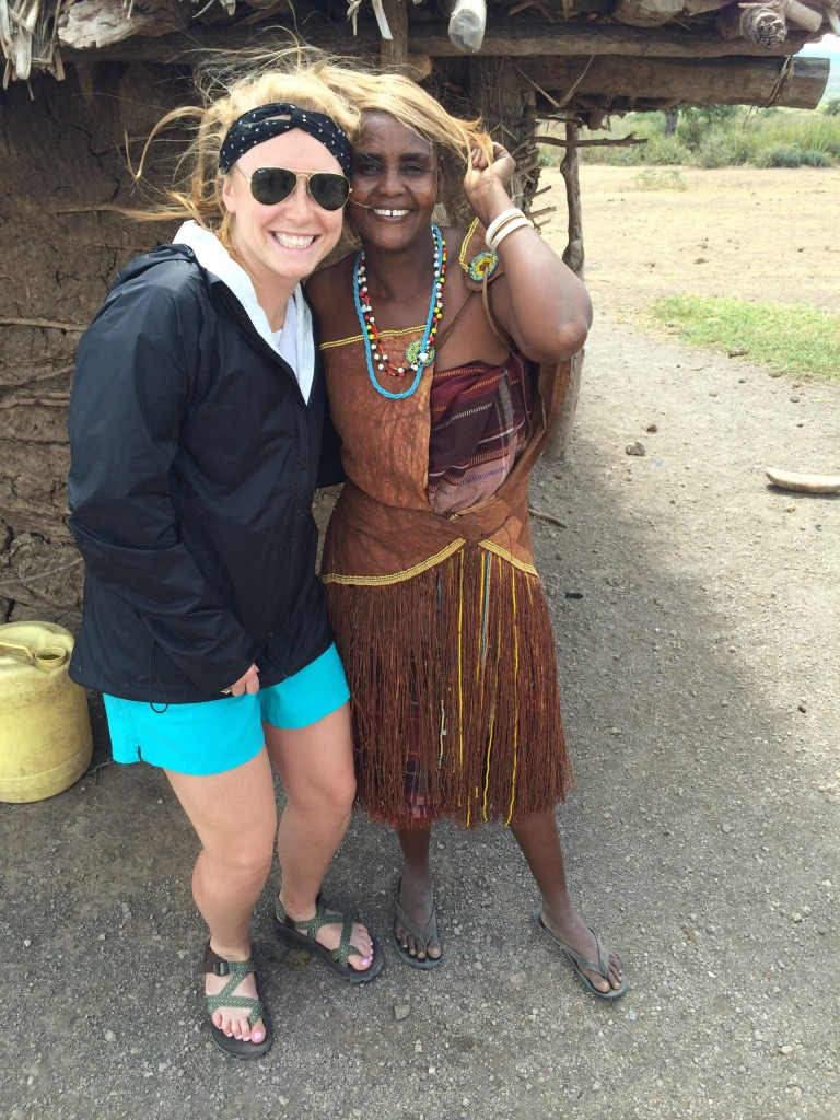 blond young adult woman poses with member of the Datoga tribe, who has put her hair on top of her head.