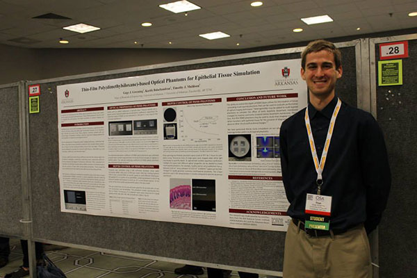 Male student stands in front of research poster, at a conference.