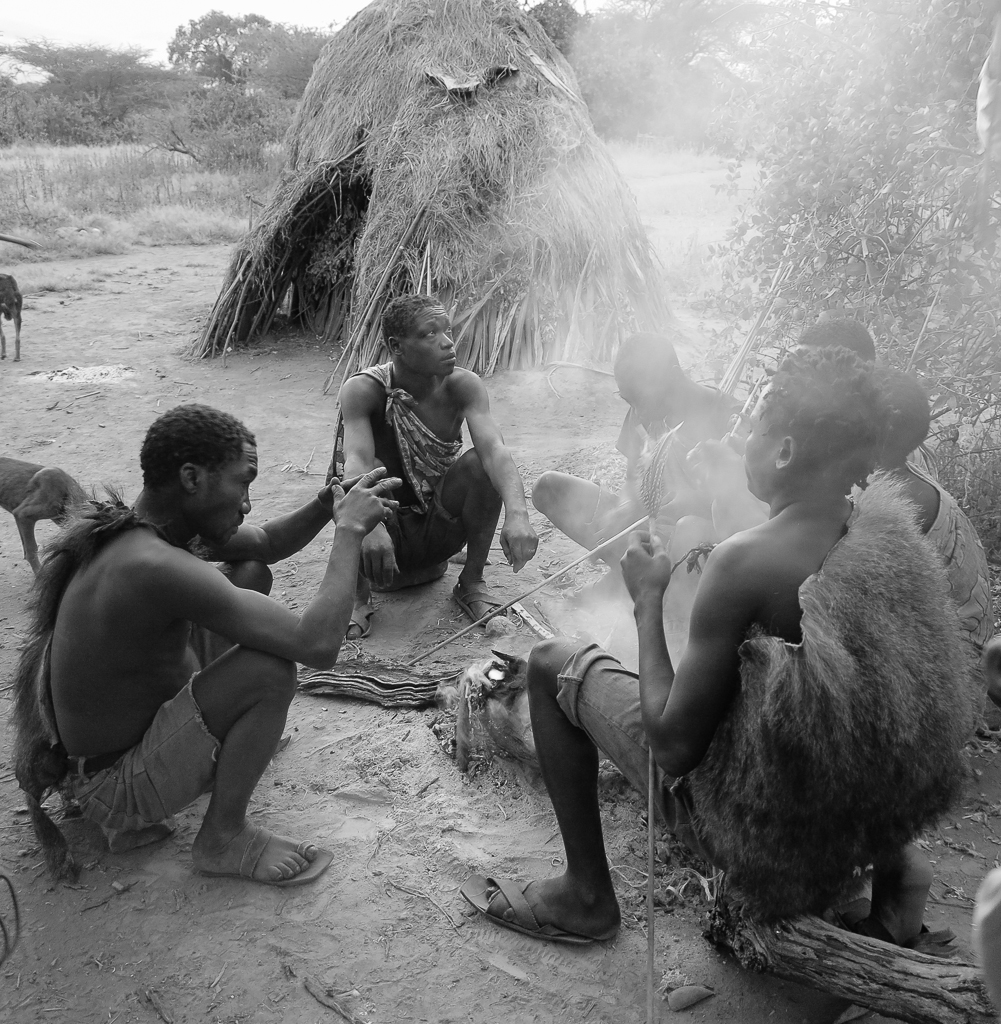 Members of the Hadzabe sit around a fire, cooking their morning's breakfast.
