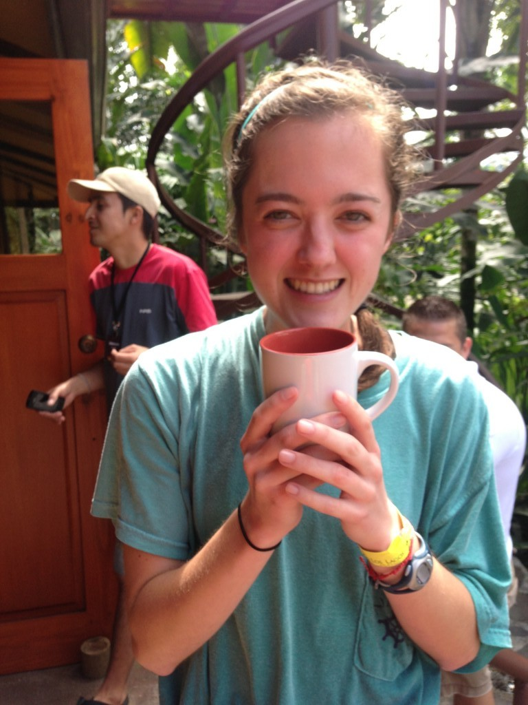 girl holding a cup of coffee in a tropical environment