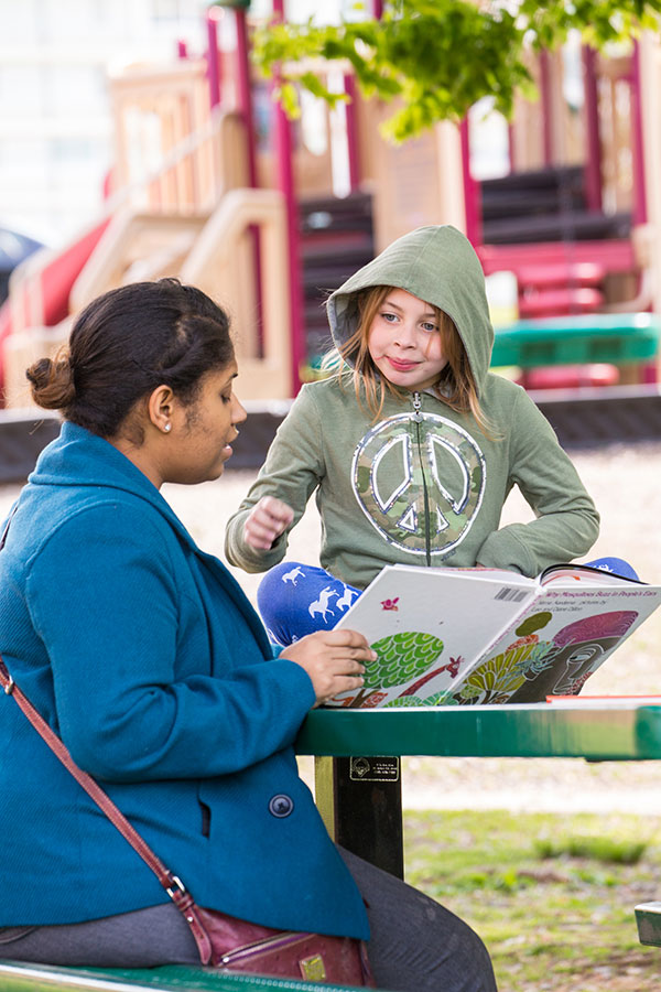 A young woman reads a book to a little girl wearing a hoodie; playground equipment visible in back.