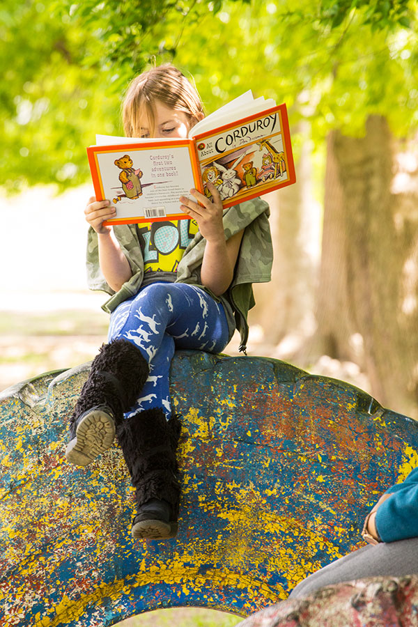 A little girl is reading the picture book Corduroy perched on a tractor tire.
