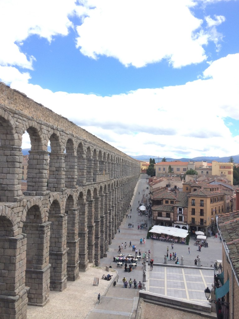 A bright photo of the Aqueduct of Segovia on a sunny summer day.