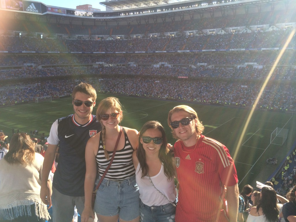 Four students pose at a soccer stadium in Spain.