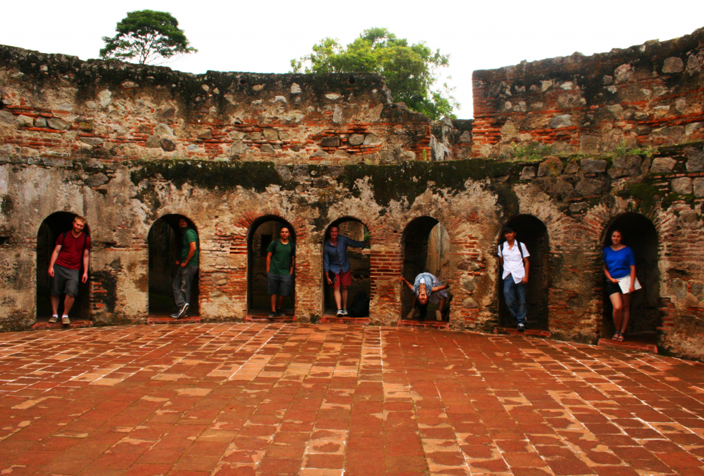 The group takes a picture within a unique monastery that has cells arrange around a circular courtyard.