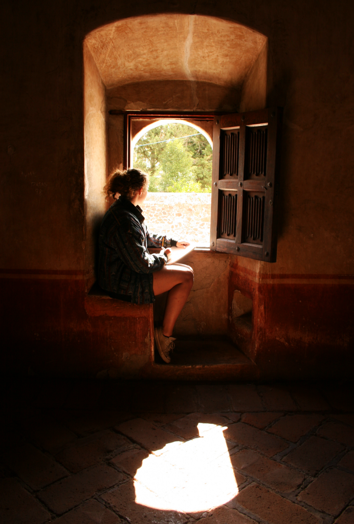 A woman looks out a window and sketches.