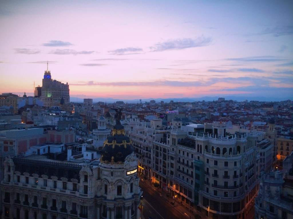 Photo of a colorful sunset over Madrid from El Círculo de Bellas Artes, which shows the buildings and city below.