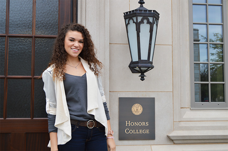 A young woman is standing by the door to the Honors College home in Ozark Hall.