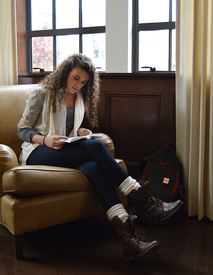 A young woman is studying in a comfortable chair in front of a window.