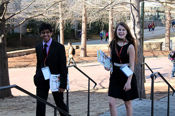 A young man and woman in formal dress are walking on campus.