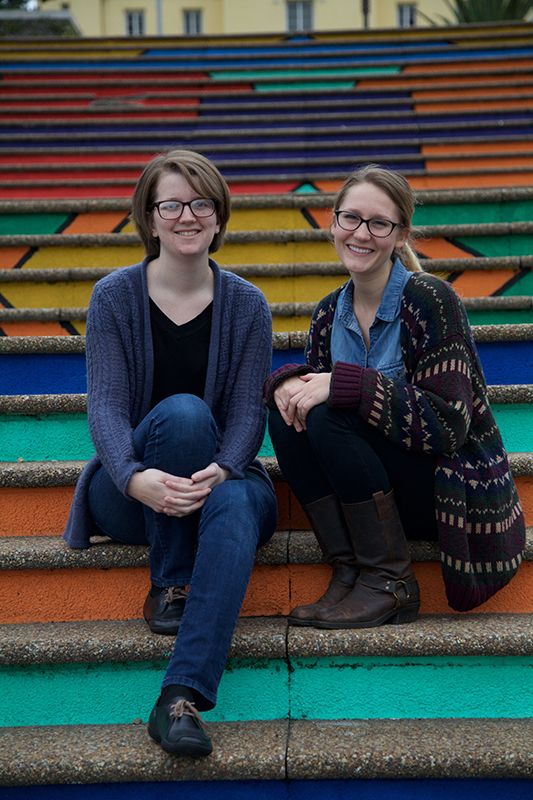 Two young women are seated on brightly panted steps.